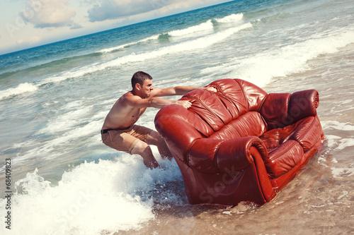 Foto man dragging vintage sofa into sea