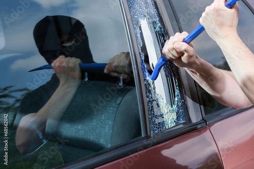 Canvas Print Robber with crowbar smashing glass