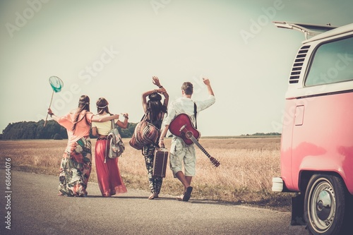фотография Multi-ethnic hippie friends with guitar and luggage