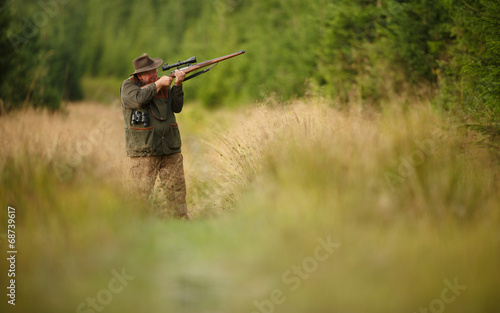 hunter with his rifle in spring forest, hunter holding a rifle Fototapeta