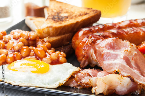 Fotografering Full English breakfast with bacon, sausage, egg and beans