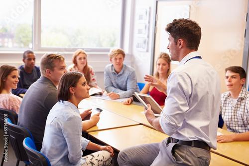 Carta da parati Teacher With College Students Giving Lesson In Classroom
