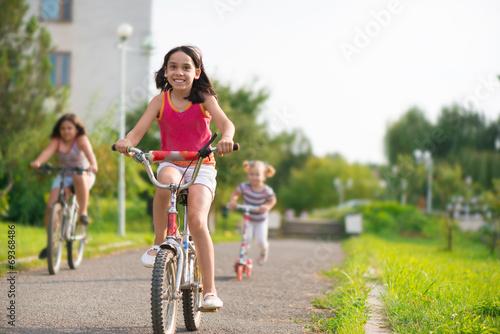 Obraz na płótnie Three happy children riding on bicycle