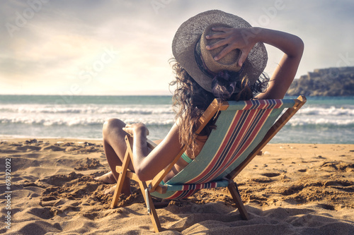 Photographie young woman who is taking the sun on the beach
