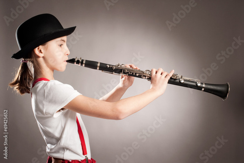 Valokuva little girl playing clarinet on a gray background