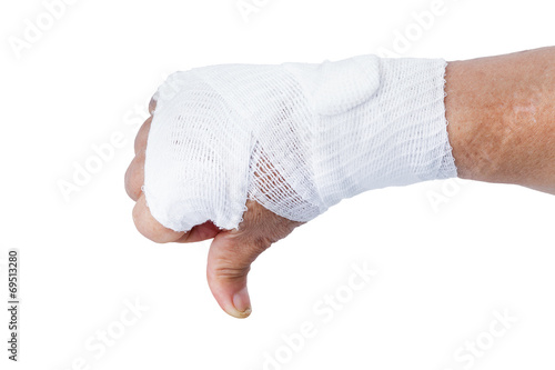 Fotografie, Tablou Thumb down showing by hand with white bandages isolated