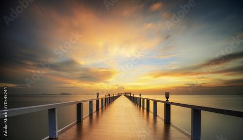 Naklejka premium Lesisty most w porcie między wschodem słońca.