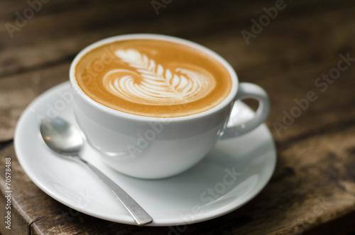 Billede på lærred Foamy latte coffee on dark grained wood table form above