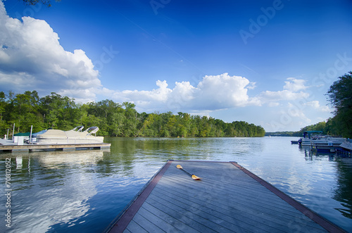 Stampa su Tela boats at dock on a lake with blue sky