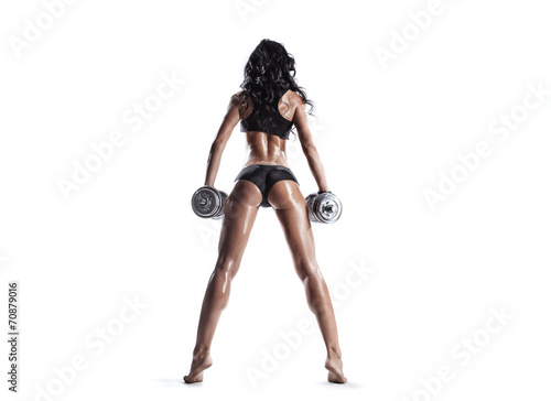 sexy muscled fitness brunette girl posing with dumbbells