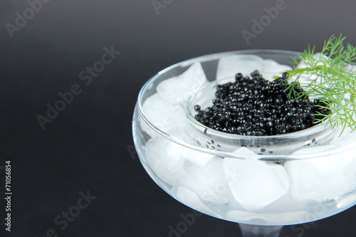 Glass bowl of black caviar and ice in goblet on dark background
