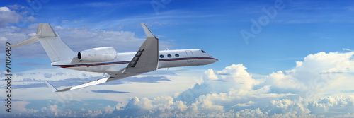 Fototapeta Corporate jet cruising in a cloudy sky