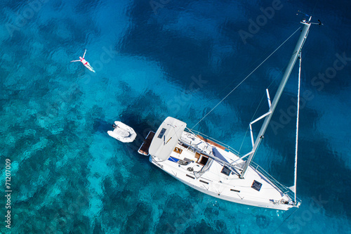 Fotografia yacht and swimming woman and clear water - caribbean paradise