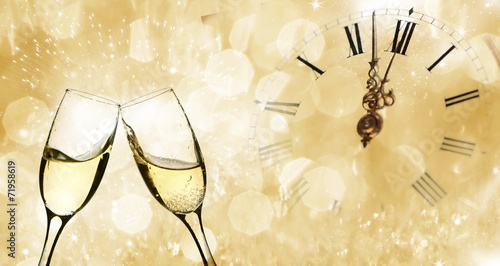 Glasses with champagne and clock close to midnight