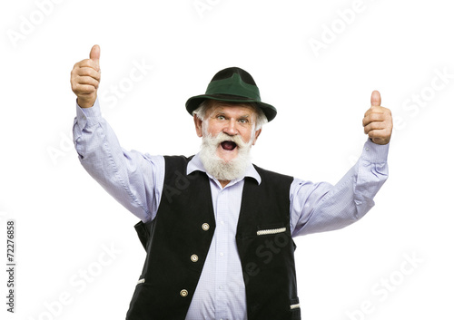 Foto Old bavarian man in hat with thumbs up isolated