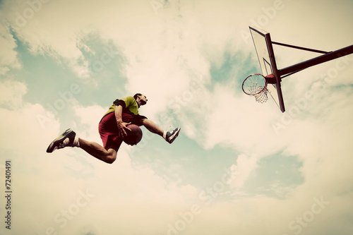 Canvas Print Young man making slam dunk playing streetball, basketball