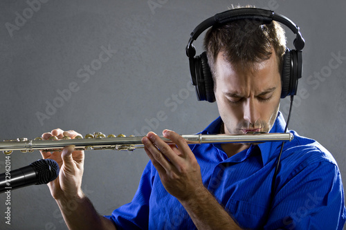male flute player in a recording studio with headphones Fototapeta
