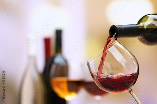 Obraz na plátne Red wine pouring into wine glass, close-up