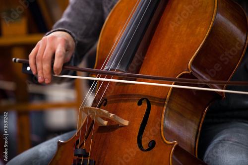 Billede på lærred Detail of the cello in the hands of a musician