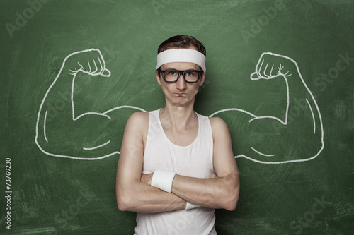Photo Funny sport nerd with fake muscle drawn on the chalkboard