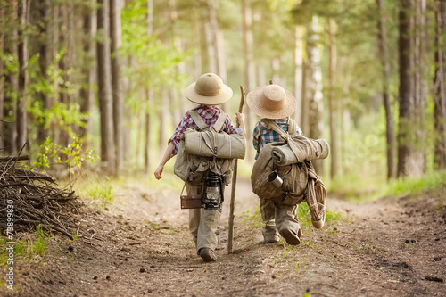Canvas Print Boys on a forest road with backpacks