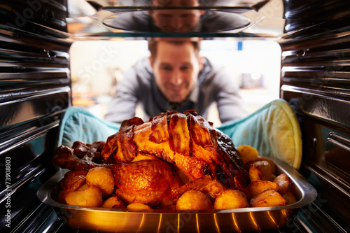 Tablou Canvas Man Taking Roast Turkey Out Of The Oven