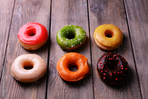 Canvas Print Delicious donuts with glaze on wooden background