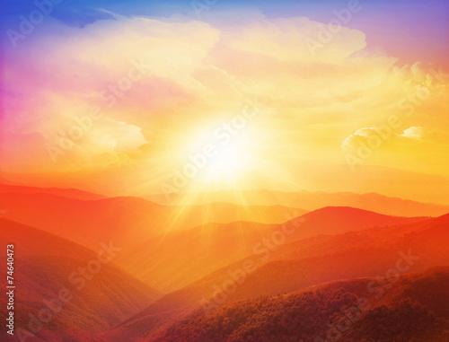 Majestatyczny zmierzch w góra krajobrazie z pogodnymi promieniami.