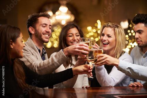 Cuadros en Lienzo Group Of Friends Enjoying Evening Drinks In Bar