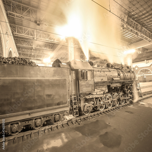Steam train arrives to the station at night time.
