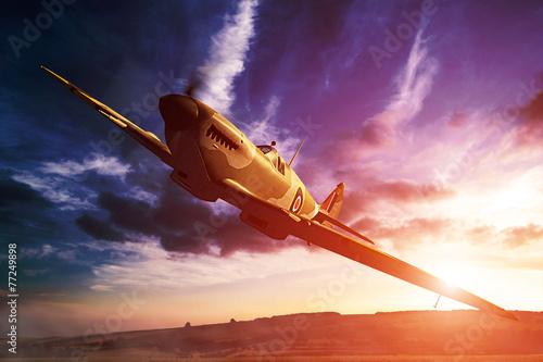 Fotografering Supermarine Spitfire in fligjt with clouds during sunset