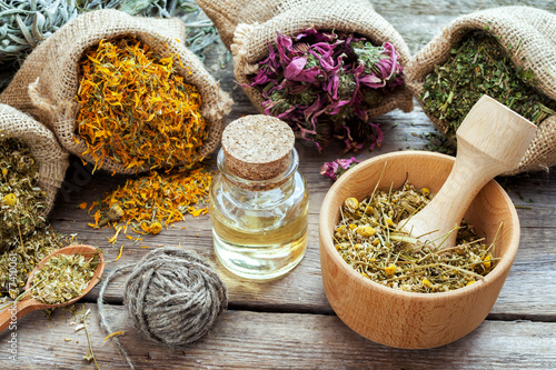 Fotografie, Tablou Healing herbs in hessian bags, mortar with chamomile and essenti