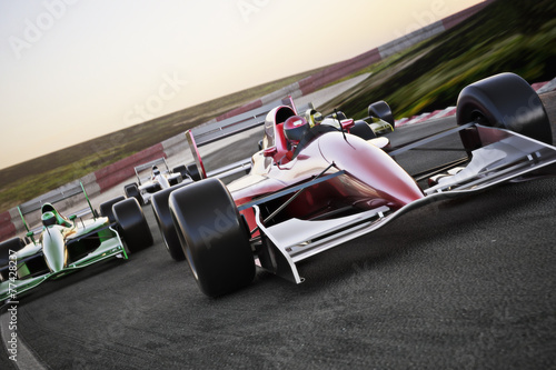 Photo Red race car close up front view on a track leading the pack