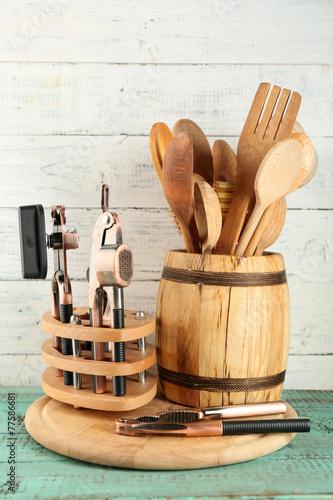 Different utensils in wooden barrel