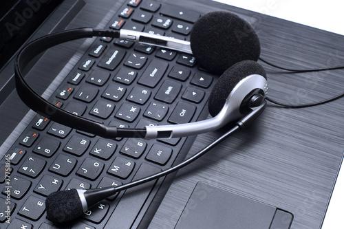 Headset lying on a laptop computer keyboard Fototapeta