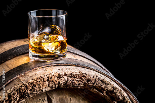 Fotografia Glass of whisky with ice on old wooden barrel
