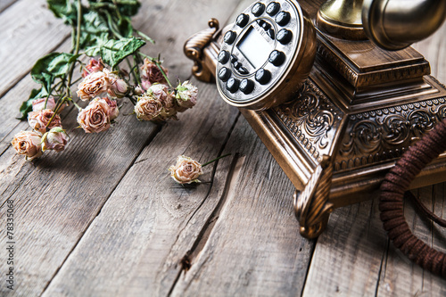 Old vintage black rotary phone and a bouquet of roses #78335068