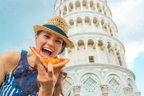 Fotografia Happy young woman eating pizza in front of leaning tower of pisa
