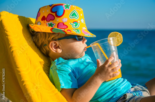 Chłopiec dzieciak w fotelu z soku szkłem na plaży