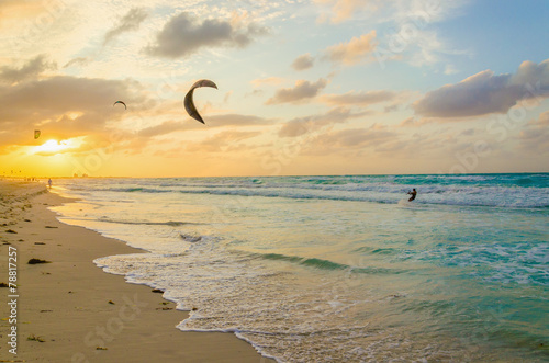 Professional kiter makes the difficult trick on a sunset beach