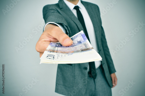 Fotografering man giving a wad of pound sterling bills to the observer