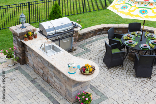 Carta da parati Outdoor kitchen and dining table on a paved patio