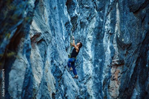 Canvas Print Rock climber climbing up a cliff