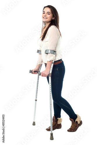 Fotografia Full length portrait of young girl walking with crutches