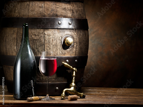 Still-life with glass of wine, bottle and barrel.