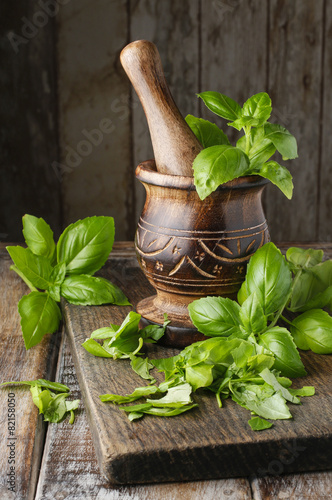 Tableau sur Toile Wooden mortar and basil leaves on the table
