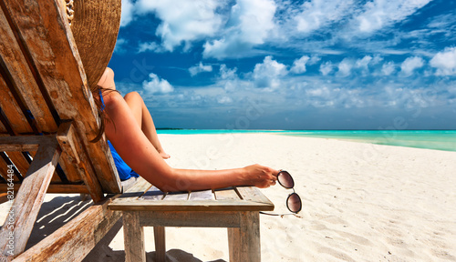 Fotografia Woman at beach holding sunglasses