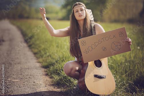 Obraz na plátně Beautiful hippie hitch-hiker with guitar