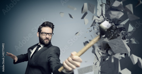 Fotografia, Obraz Young boss smashing a wall with a hammer