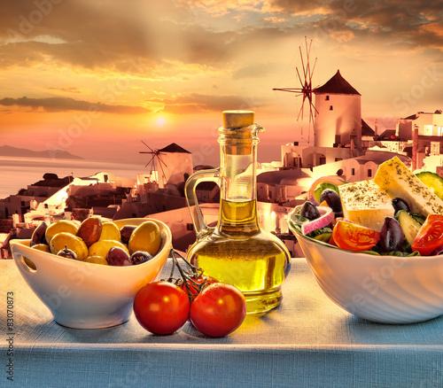 Greek salad against windmill in  Santorini island in Greece